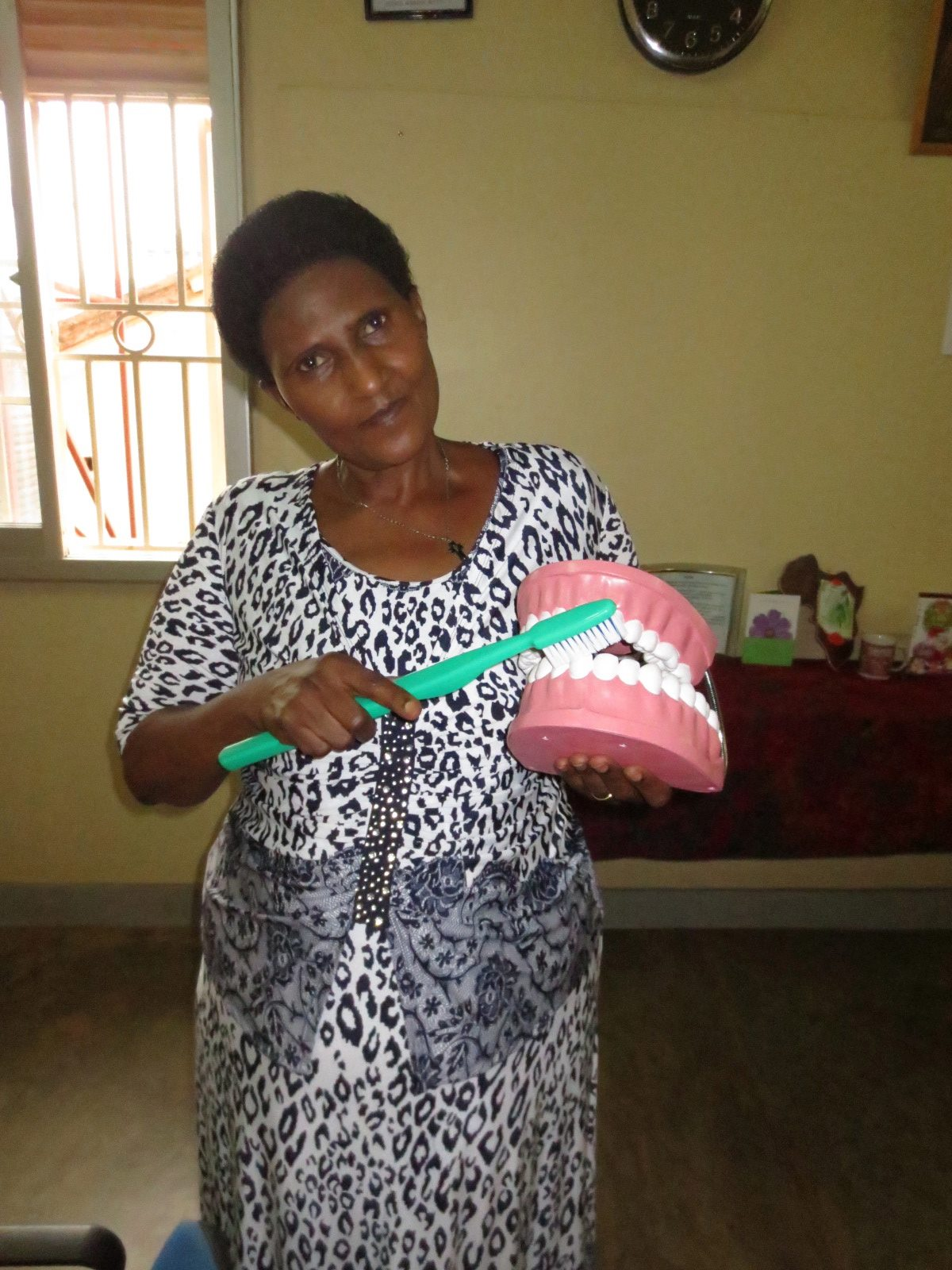 """Mama"" Noelina, founder of Meeting Point Kampala, with a new tooth and brush model donated by PHS."